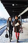 Young female friends in warm clothing walking on station platform Stock Photo - Premium Royalty-Free, Artist: Blend Images, Code: 698-06616255