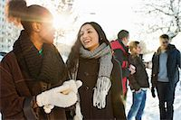 Happy young women in warm clothing with male friends in background Stock Photo - Premium Royalty-Freenull, Code: 698-06616269