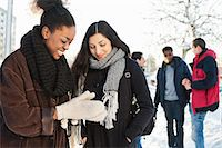 Happy young female friends in warm clothing with men in background Stock Photo - Premium Royalty-Freenull, Code: 698-06616270