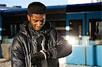African American young man checking time at railway station Stock Photo - Premium Royalty-Free, Artist: Blend Images, Code: 698-06616284