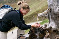 hiker takes water from wooden well Stock Photo - Premium Royalty-Freenull, Code: 618-06618471