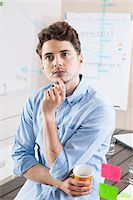 Young Man Working in an Office, Looking Through Glass Board, Germany Stock Photo - Premium Royalty-Freenull, Code: 600-06620955