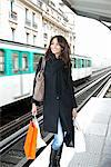 Woman carrying shopping bags on platform Stock Photo - Premium Royalty-Free, Artist: Jason Friend, Code: 649-06621970