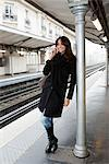 Woman on cell phone at train station Stock Photo - Premium Royalty-Free, Artist: Westend61, Code: 649-06621972