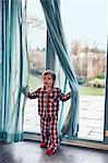 Boy in pajamas playing in curtain Stock Photo - Premium Royalty-Free, Artist: Blend Images, Code: 649-06622413