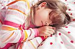 Girl sleeping on polka dot blanket Stock Photo - Premium Royalty-Free, Artist: CulturaRM, Code: 649-06622423