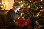 Smiling boy opening Christmas present Stock Photo - Premium Royalty-Free, Artist: Blend Images, Code: 649-06622461