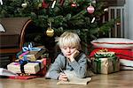 Boy writing under Christmas tree Stock Photo - Premium Royalty-Free, Artist: Blend Images, Code: 649-06622467