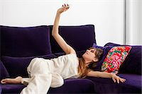 Woman taking picture of herself on sofa Stock Photo - Premium Royalty-Freenull, Code: 649-06622540