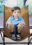 Boy crouching in camp chair Stock Photo - Premium Royalty-Free, Artist: Uwe Umstätter, Code: 649-06622587