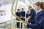 Teacher demonstrating nautical knots Stock Photo - Premium Royalty-Free, Artist: Blend Images, Code: 649-06622843