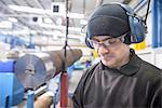 Worker wearing headphones in factory Stock Photo - Premium Royalty-Free, Artist: Blend Images, Code: 649-06622902