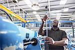 Worker checking machinery in factory Stock Photo - Premium Royalty-Free, Artist: Blend Images, Code: 649-06622941