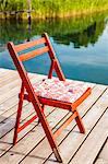 Chair on wooden pier over lake Stock Photo - Premium Royalty-Free, Artist: Blend Images, Code: 649-06623005