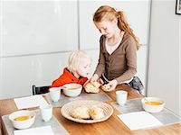family table eating together - Girl serving brother lunch at table Stock Photo - Premium Royalty-Freenull, Code: 649-06623058