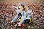 Girl in fairy wings playing in leaves Stock Photo - Premium Royalty-Free, Artist: Blend Images, Code: 649-06623086
