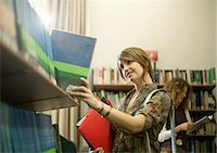 selecting - Student searching for book in library Stock Photo - Premium Royalty-Freenull, Code: 614-06623338