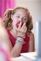 preteen girl pigtails - Girl eating apple at desk Stock Photo - Premium Royalty-Freenull, Code: 614-06623446