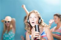 Girl singing into hairbrush Stock Photo - Premium Royalty-Freenull, Code: 614-06623492