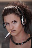 Teenage girl in dark makeup smoking Stock Photo - Premium Royalty-Freenull, Code: 614-06623596