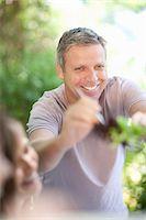 Man serving himself salad at table Stock Photo - Premium Royalty-Freenull, Code: 614-06623605