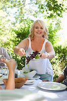 Woman serving salad at table outdoors Stock Photo - Premium Royalty-Freenull, Code: 614-06623607