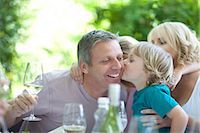 Boy kissing father at table outdoors Stock Photo - Premium Royalty-Freenull, Code: 614-06623612