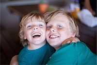preteen open mouth - Smiling boys hugging in living room Stock Photo - Premium Royalty-Freenull, Code: 614-06623658