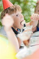 preteen open mouth - Boy having ice cream sundae at party Stock Photo - Premium Royalty-Freenull, Code: 614-06623763
