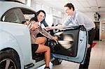Woman getting in car at dealership Stock Photo - Premium Royalty-Free, Artist: Blend Images, Code: 614-06623976