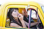 Woman fixing makeup in car mirror Stock Photo - Premium Royalty-Free, Artist: Blend Images, Code: 614-06624123