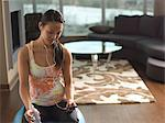 Woman with earphones on exercise ball Stock Photo - Premium Royalty-Free, Artist: Aflo Relax, Code: 614-06624256