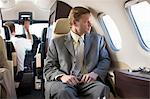 Businessman sitting in airplane Stock Photo - Premium Royalty-Free, Artist: Kablonk! RM, Code: 614-06624343