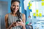Businesswoman using cell phone in office Stock Photo - Premium Royalty-Free, Artist: Uwe Umstätter, Code: 614-06624417