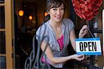 Woman hanging open sign on door Stock Photo - Premium Royalty-Free, Artist: Artiga Photo, Code: 614-06624441