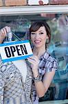 Woman hanging open sign on mannequin Stock Photo - Premium Royalty-Free, Artist: Blend Images, Code: 614-06624450