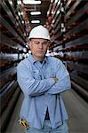 Worker standing in metal plant Stock Photo - Premium Royalty-Free, Artist: Blend Images, Code: 614-06624552