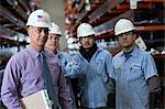Workers and businessman in metal plant Stock Photo - Premium Royalty-Free, Artist: Blend Images, Code: 614-06624561