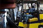 Worker using forklift in metal plant Stock Photo - Premium Royalty-Free, Artist: Blend Images, Code: 614-06624564