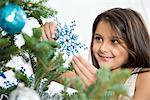 Smiling girl decorating Christmas tree Stock Photo - Premium Royalty-Free, Artist: Anna Huber, Code: 614-06624570