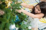 Smiling girl decorating Christmas tree Stock Photo - Premium Royalty-Free, Artist: Blend Images, Code: 614-06624576