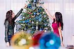 Teenage girls decorating Christmas tree Stock Photo - Premium Royalty-Free, Artist: AWL Images, Code: 614-06624582