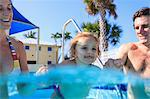 Parents swimming with toddler in pool