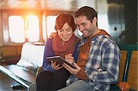 Couple using tablet computer on ferry Stock Photo - Premium Royalty-Freenull, Code: 614-06624999