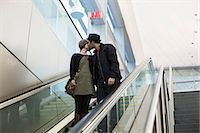 Couple kissing on escalator outdoors Stock Photo - Premium Royalty-Freenull, Code: 614-06625009