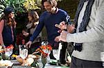 Man uncorking bottle of wine at table Stock Photo - Premium Royalty-Free, Artist: ableimages, Code: 614-06625069