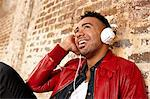 Smiling man listening to headphones Stock Photo - Premium Royalty-Free, Artist: Andrew Kolb, Code: 614-06625143