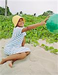 Girl playing with ball on beach Stock Photo - Premium Royalty-Free, Artist: Blend Images, Code: 614-06625203