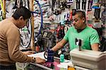 Mechanic and customer in bicycle shop Stock Photo - Premium Royalty-Free, Artist: Blend Images, Code: 614-06625224