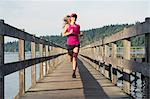 Teenage girl running on wooden dock Stock Photo - Premium Royalty-Free, Artist: Blend Images, Code: 614-06625286